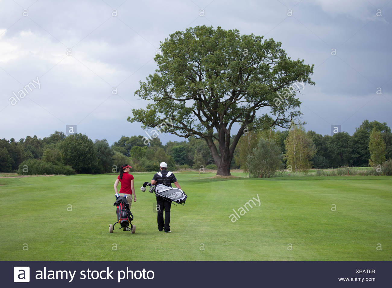 A female and male golfer walking with their golf bags, rear view Stock Photo