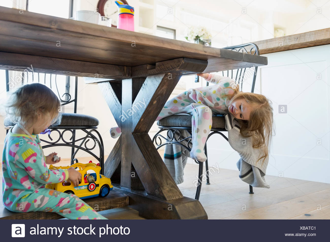 Girls in pajamas playing under dining table - Stock Image