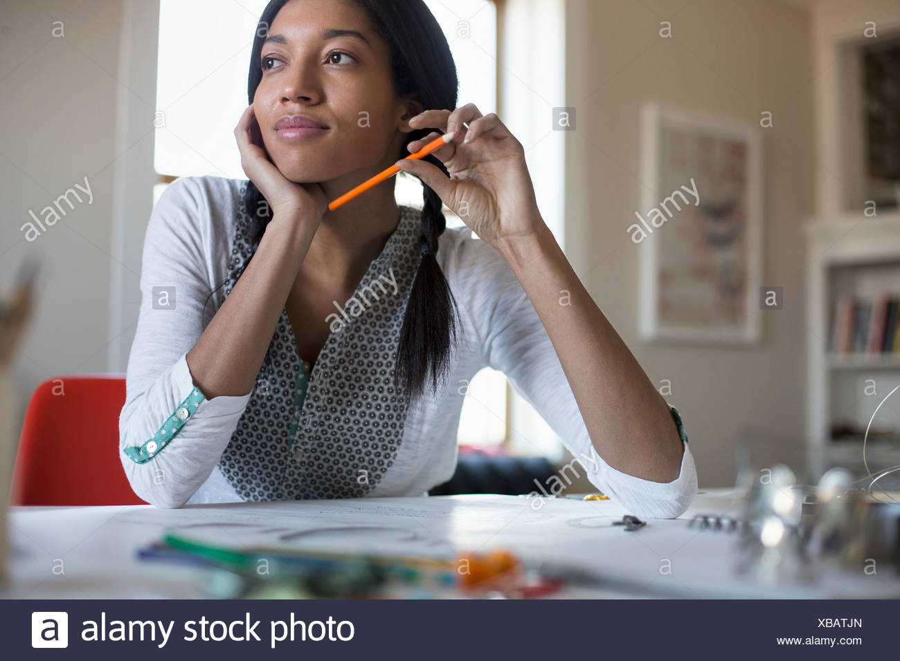 Thoughtful female jewelry artist with colored pencil at desk - Stock Image