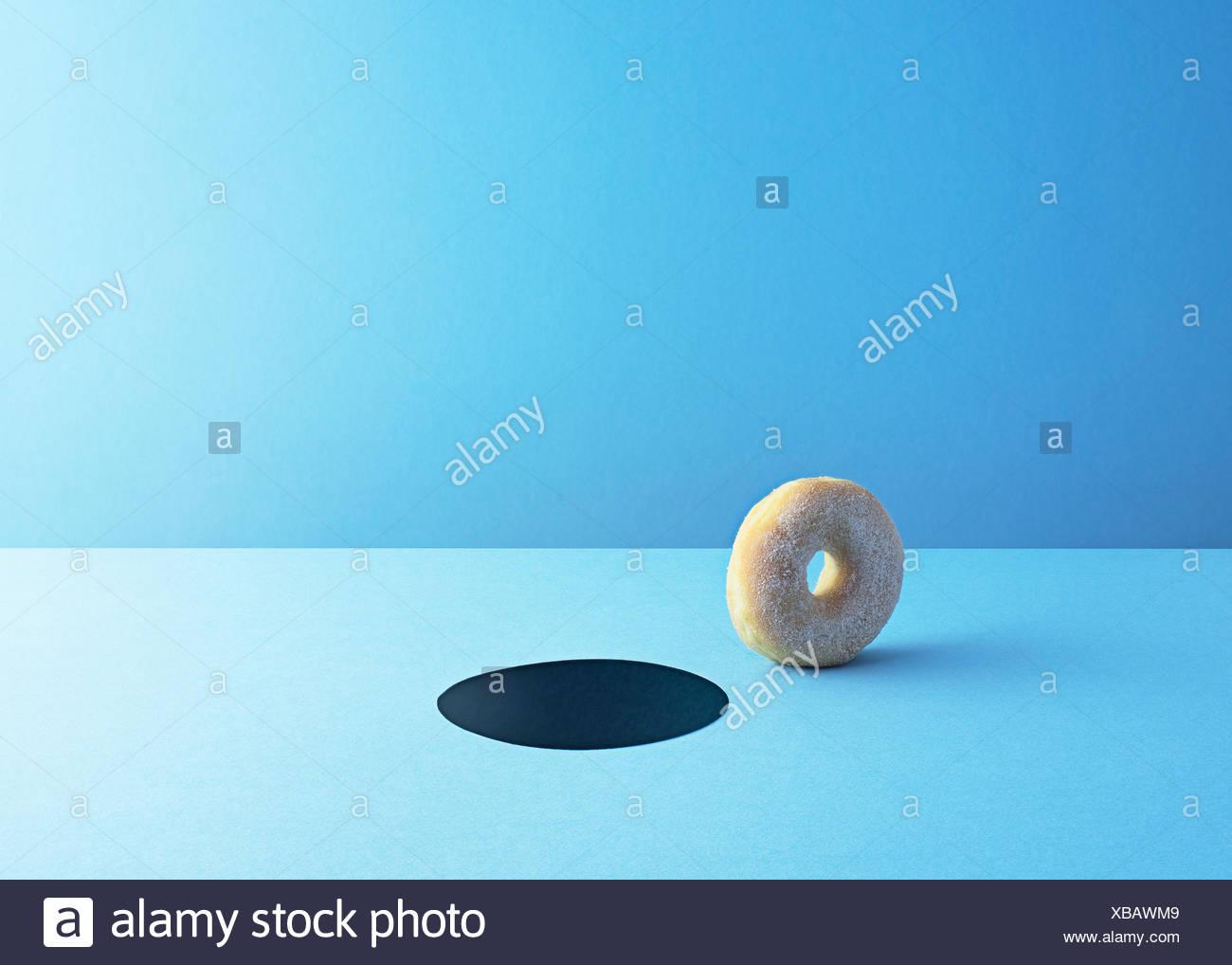 Doughnut and hole on light blue ground - Stock Image