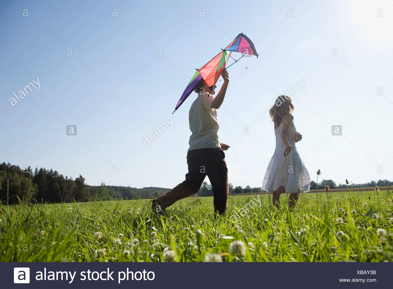 Germany, Bavaria, Young couple flying kites in meadow - Stock Image