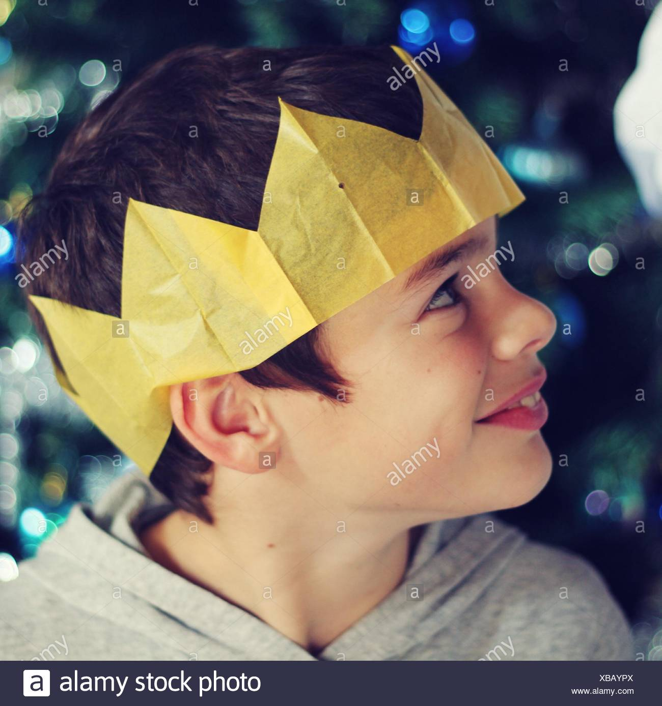 909507dc9c81d Close-Up Of Smiling Boy Wearing Paper Crown At Night During Christmas