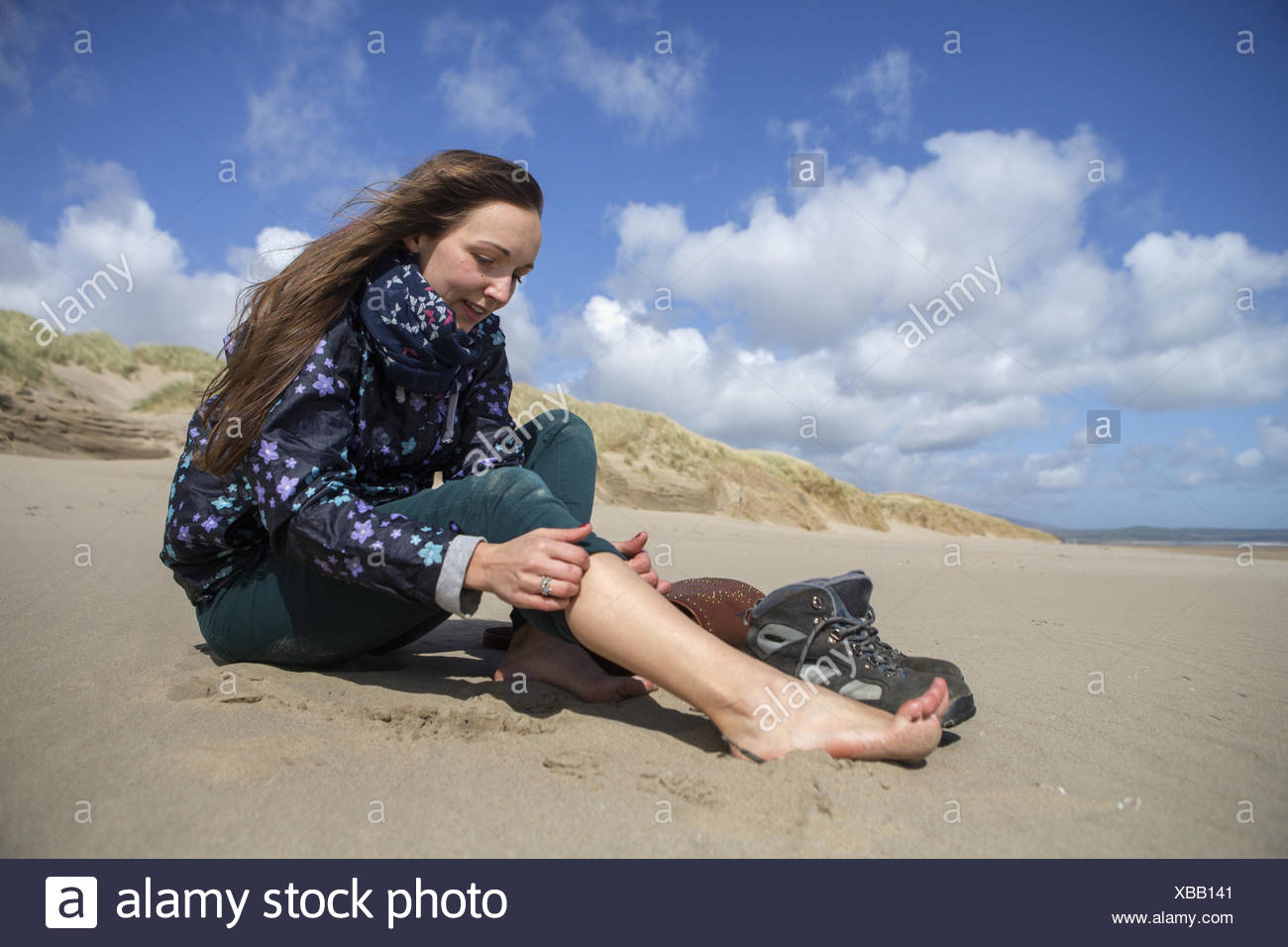 Young woman taking her hiking boots off on the beach at Harlech. - Stock Image