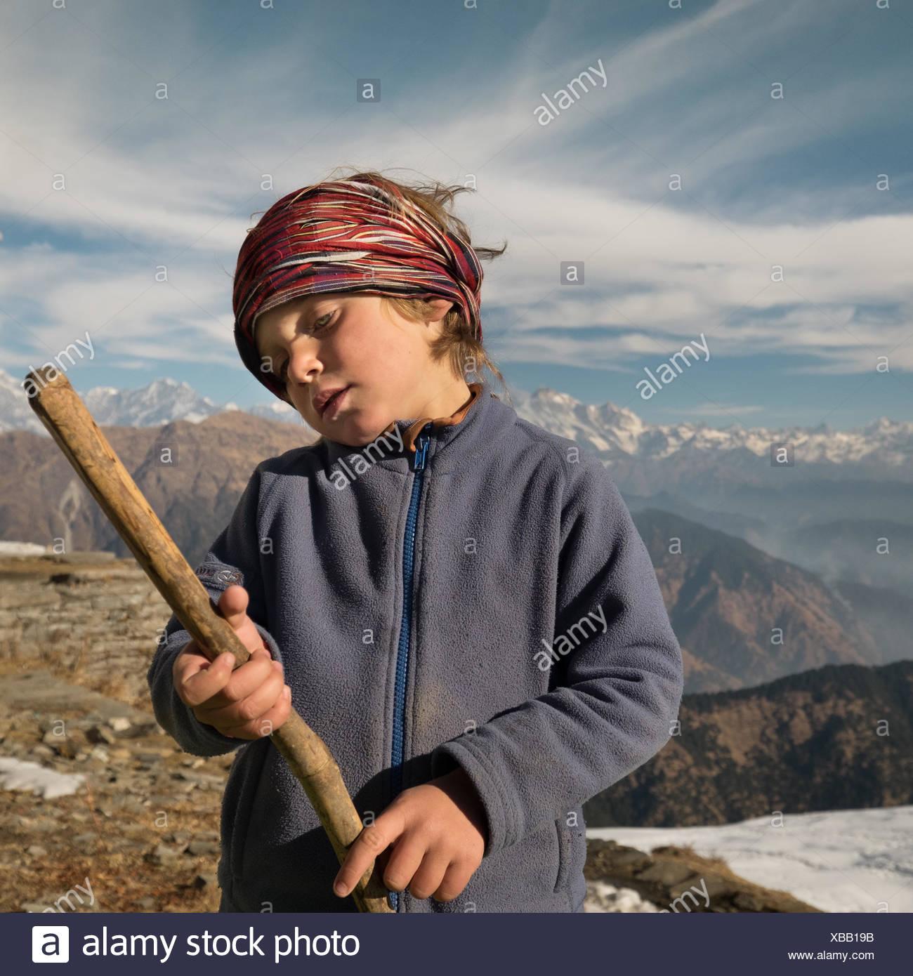 A European boy holds a wooden stick pretending it is a guitar. - Stock Image
