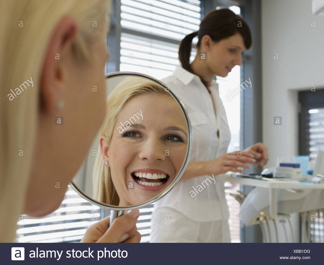 Woman admiring smile in dentist's office - Stock Image