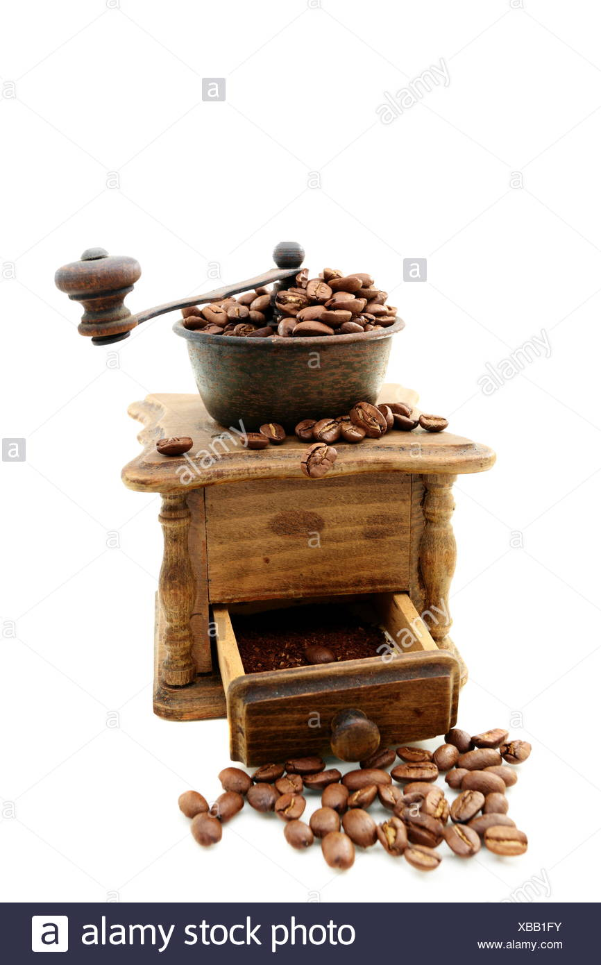 Old wooden mill with coffee beans. - Stock Image