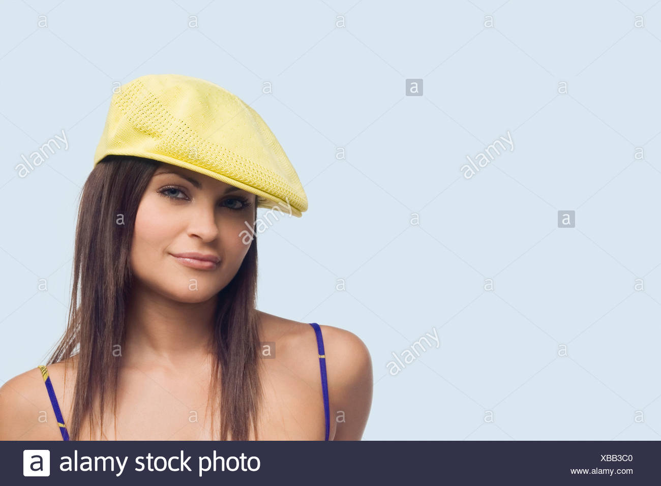 d14ffae5cc3a7 Portrait of a young woman wearing a flat cap and smirking - Stock Image