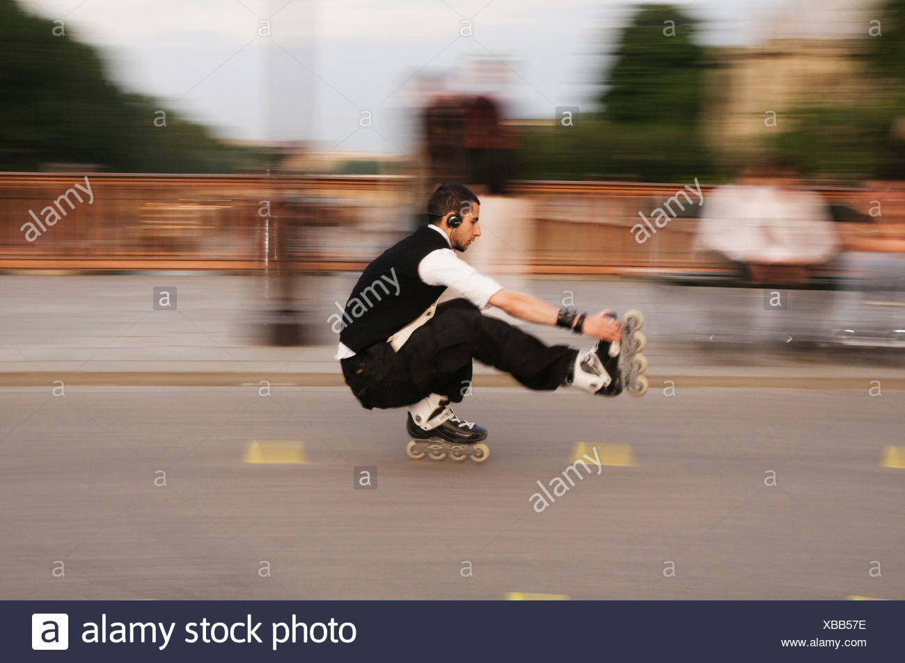 skater driving crouched on one leg, with headphones, France, Paris, Ile de France - Stock Image