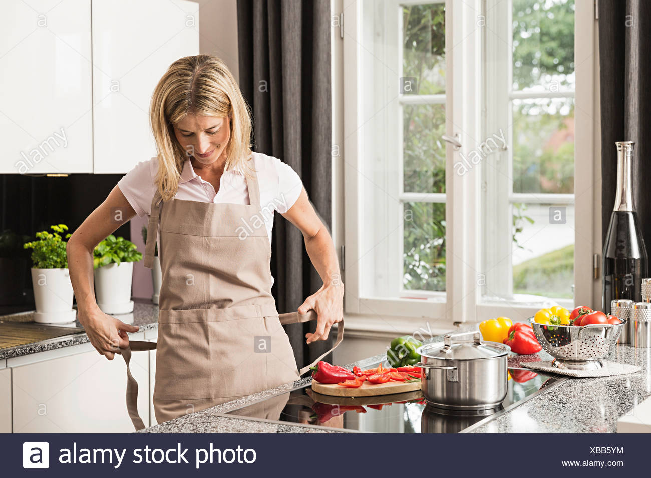 Mid adult woman tying apron in kitchen - Stock Image