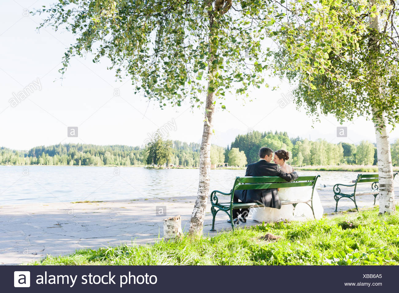 Rear view of bride and bridegroom sitting on riverside park bench - Stock Image