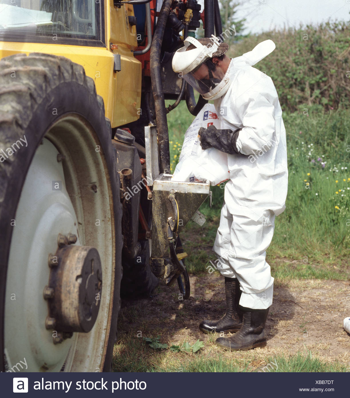 Driver of agricultural sprayer with full protective clothing filling tank with magnesium sulphate - Stock Image