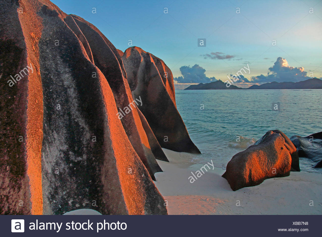beach with rutted granite rocks and view onto the island Praslin in the background, Seychelles, La Digue, Anse Source d Argent - Stock Image