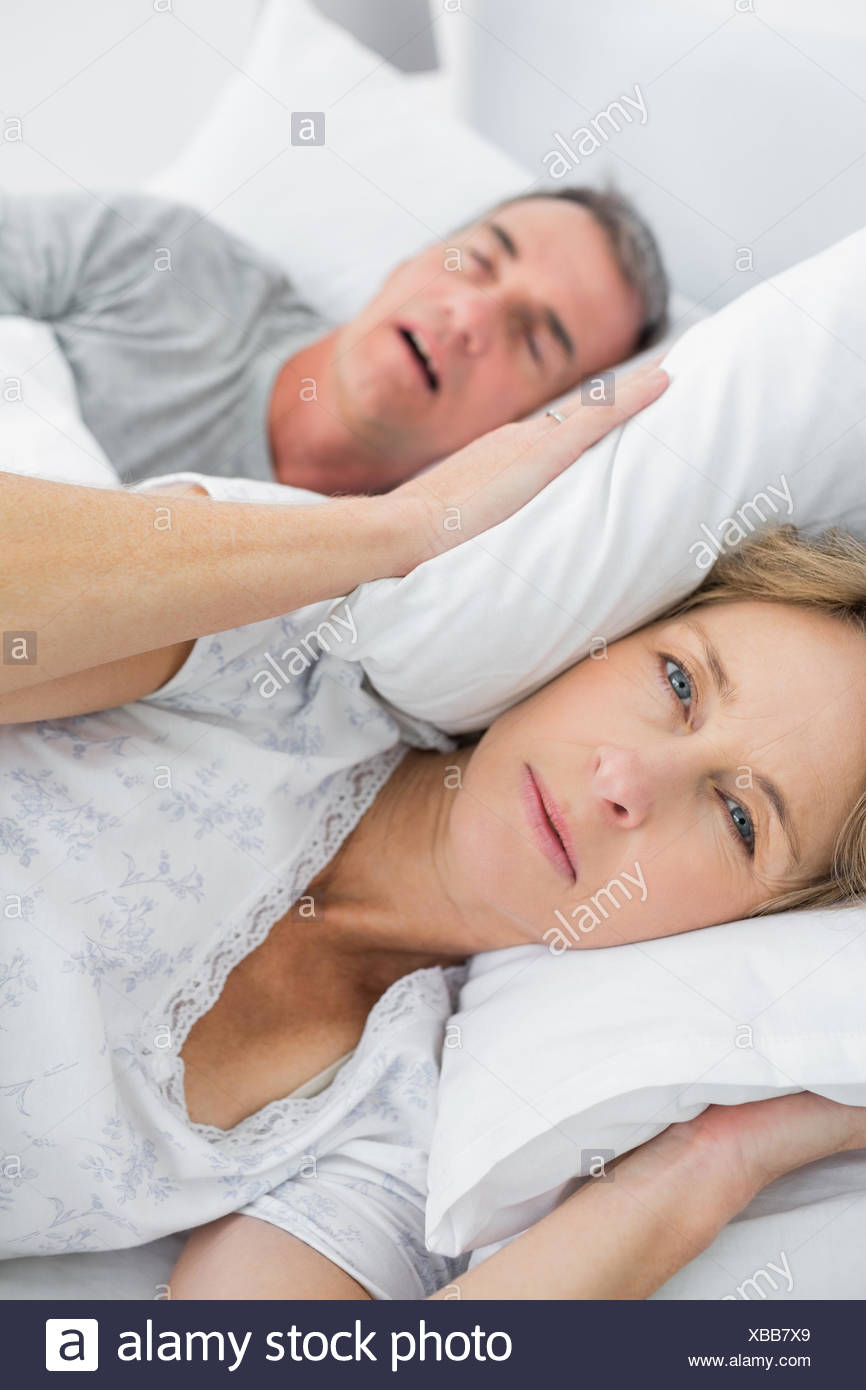 Tired wife blocking her ears from noise of husband snoring looking at camera - Stock Image