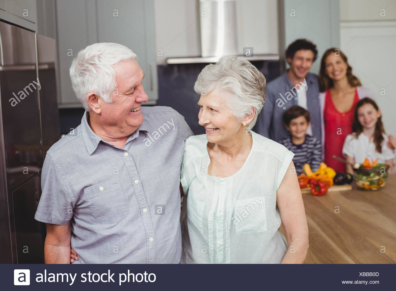 Happy grandparents with family in kitchen - Stock Image