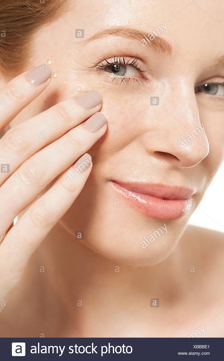 Woman applying eye gel - Stock Image