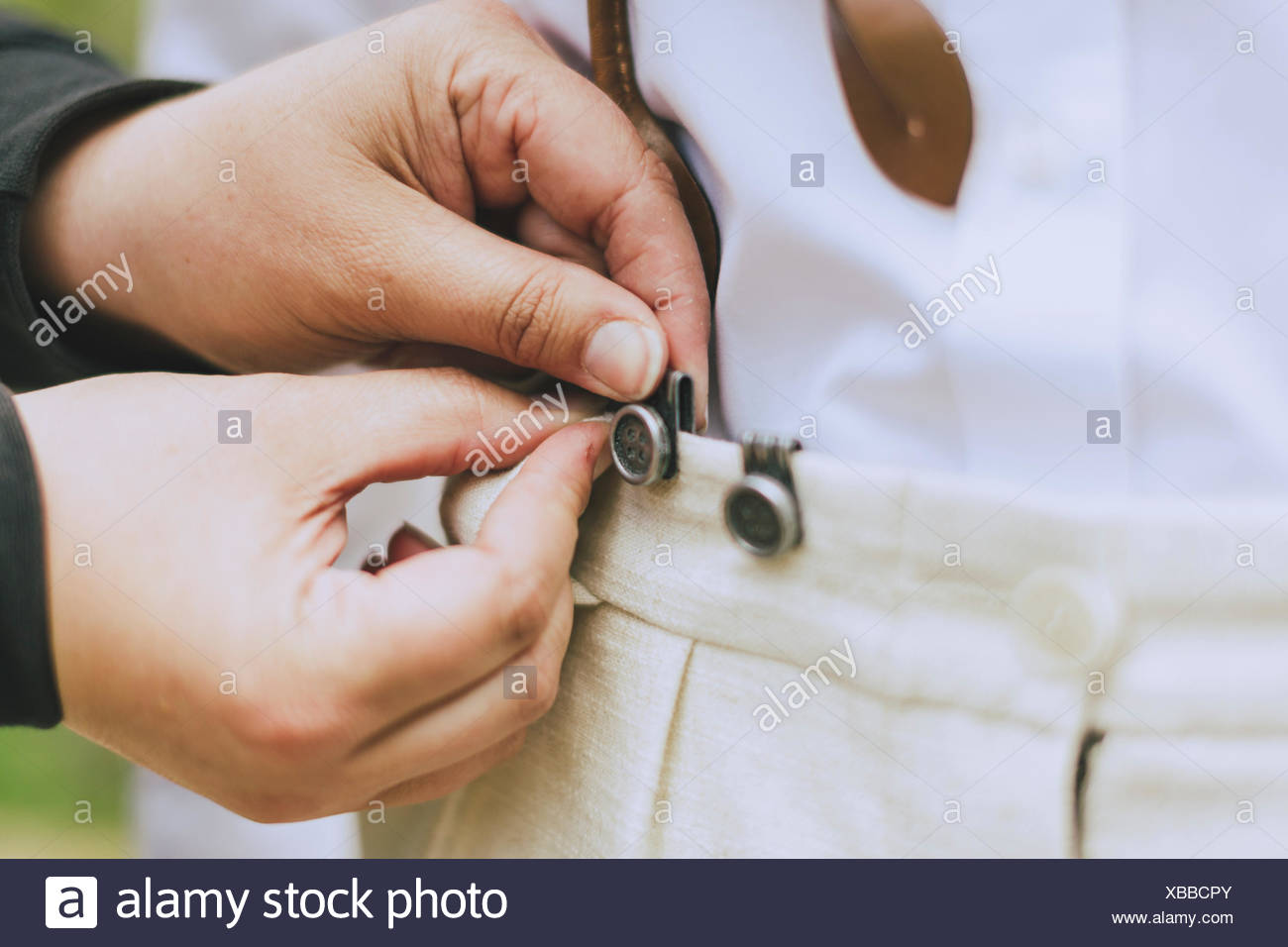 detail of the groom as his suspenders buttoned - Stock Image