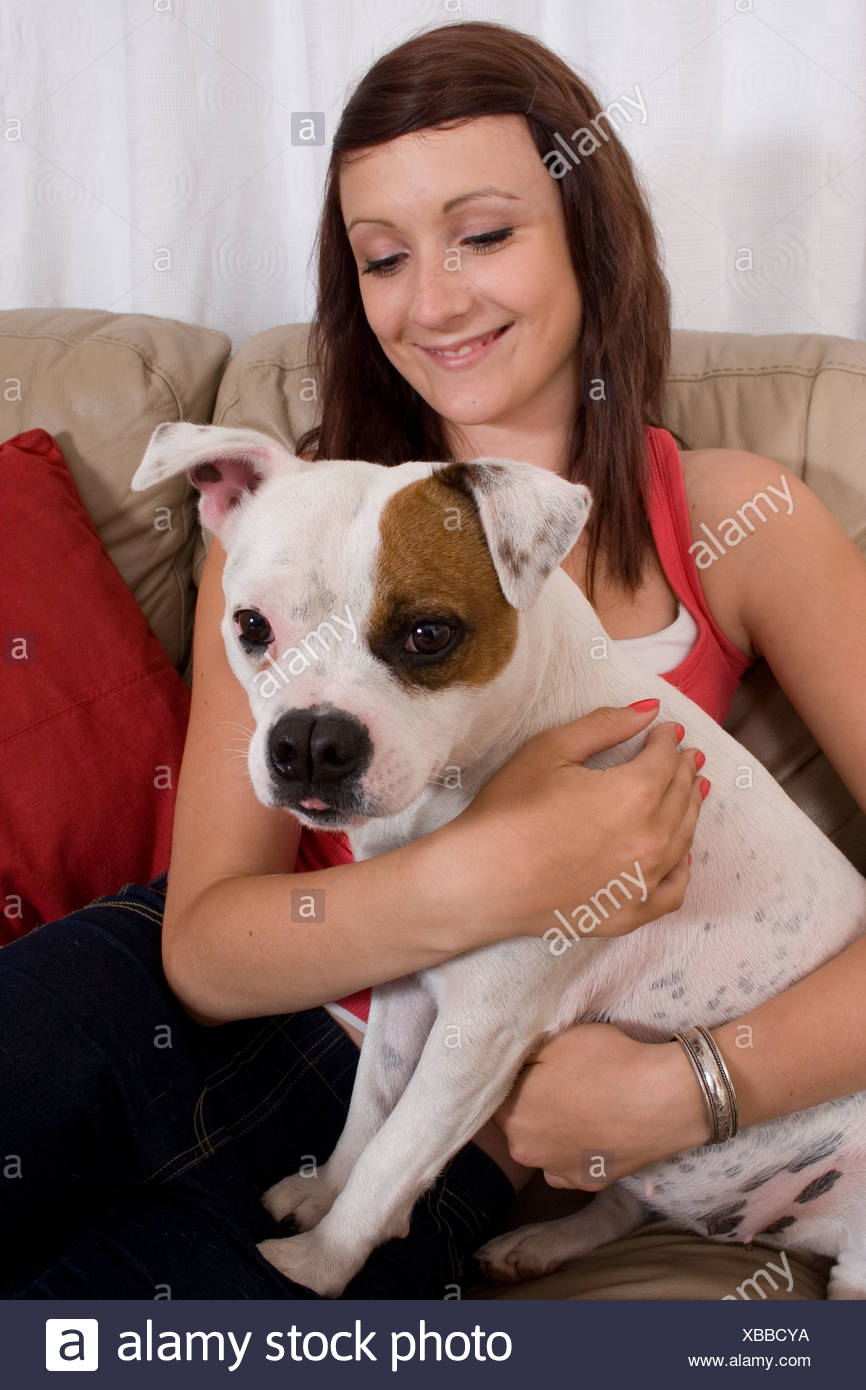 teenage girl on sofa with white staffordshire bull terrier adult dog - Stock Image