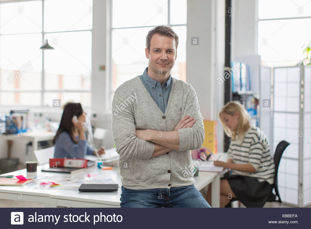 Mature man sitting on desk and smiling in creative office, portrait - Stock Image