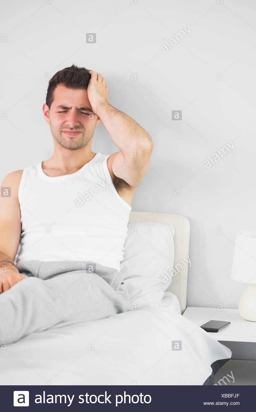Grimacing handsome man having a headache - Stock Image