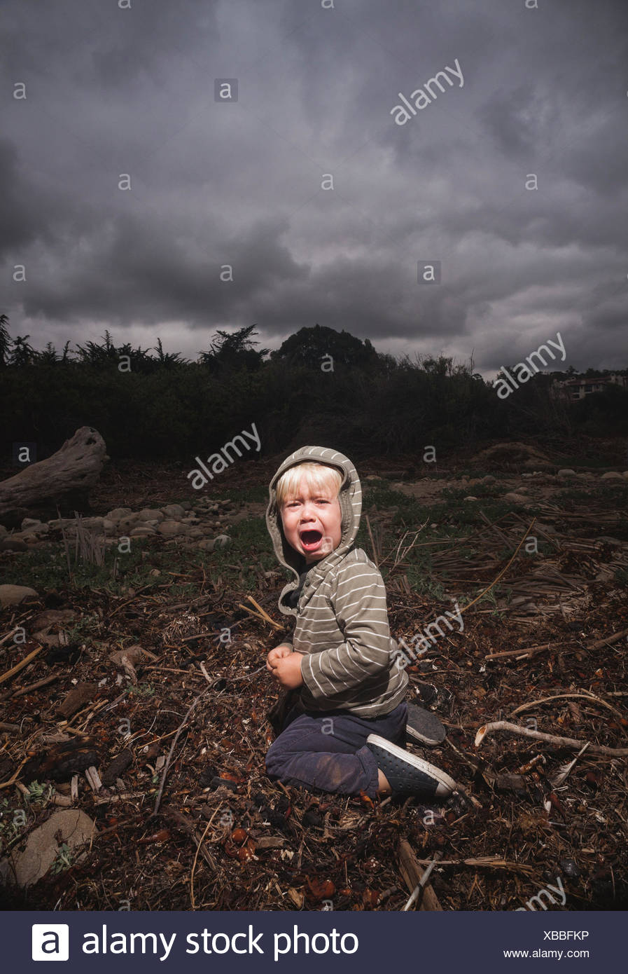 Young boy kneeling on ground crying against stormy sky Stock Photo