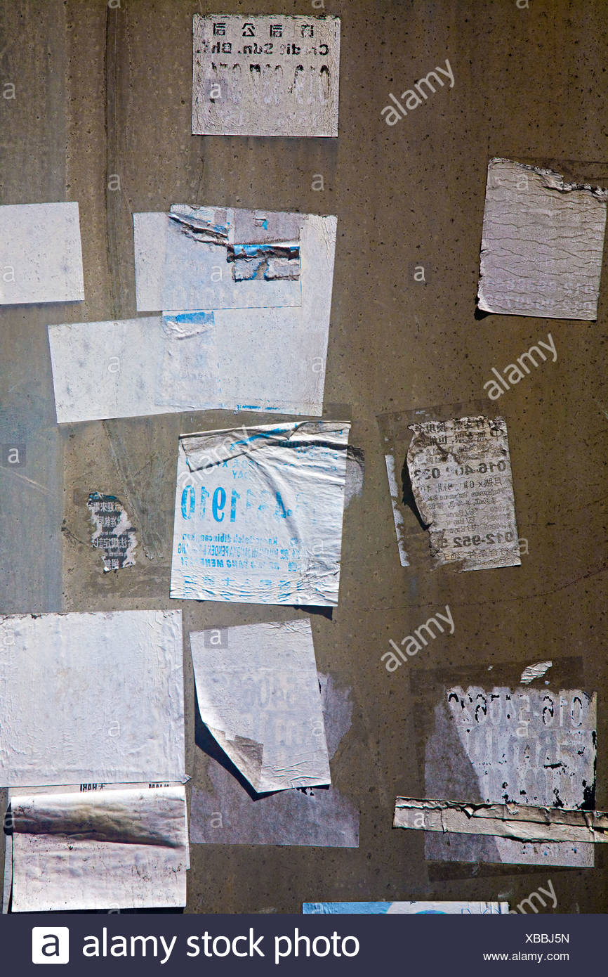 Torn stickers on a wall - Stock Image