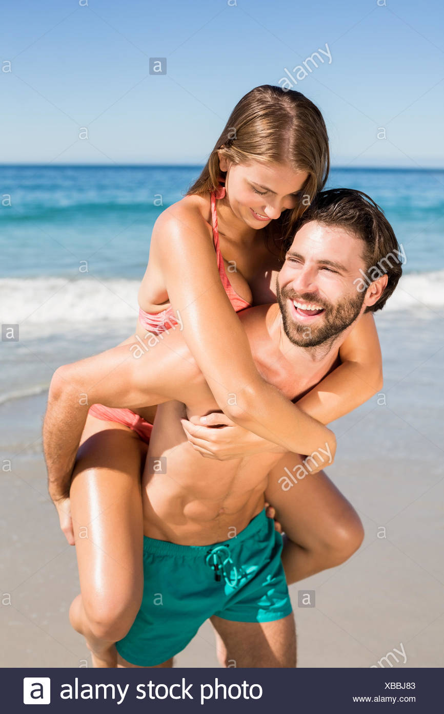 Man giving piggy back ride to woman - Stock Image