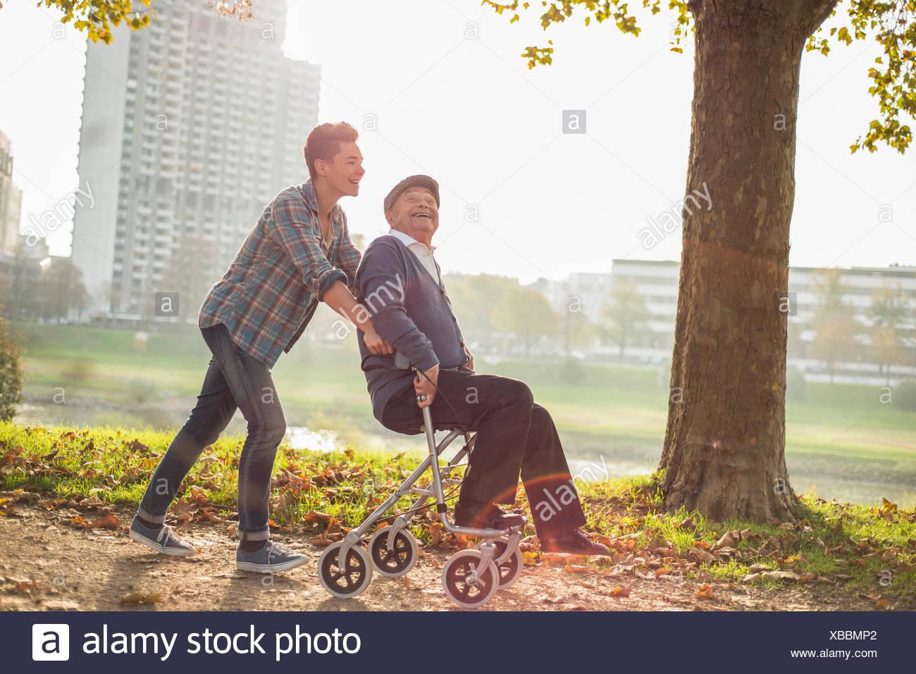 Grandson pushing happy senior man with wheeled walker - Stock Image