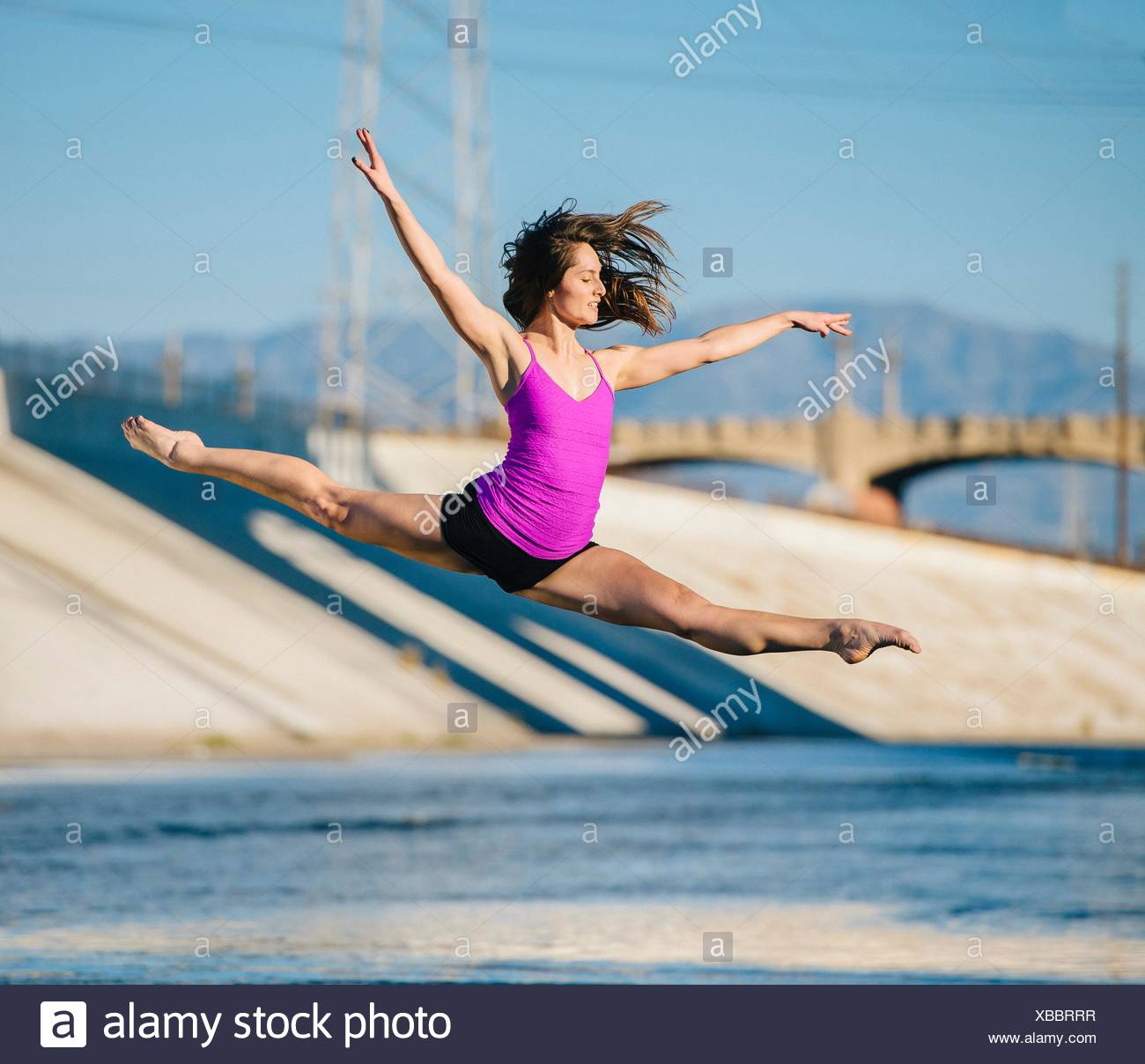 Dancer in mid air, arms raised doing the splits, Los Angeles, California, USA - Stock Image