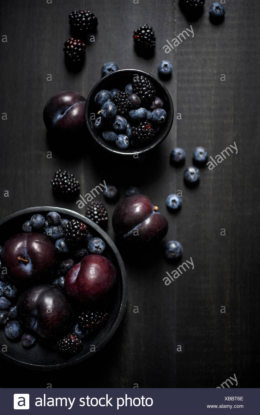 Bowls of blue and black fruits laid out artistically and beautifully on a dark wood surface. Dark and moody. - Stock Image