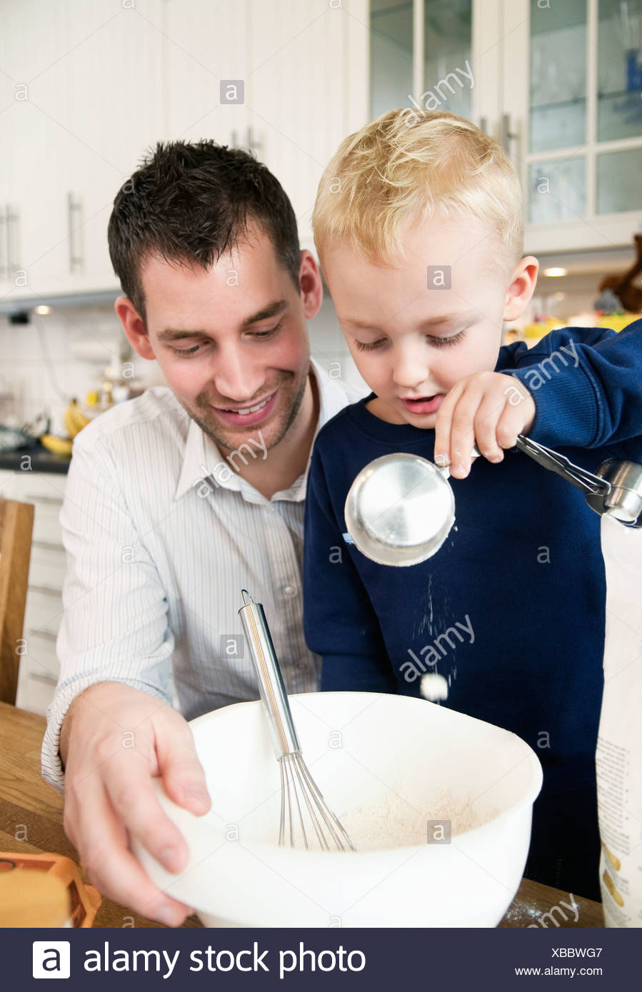 Father and child having fun in the kitchen - Stock Image