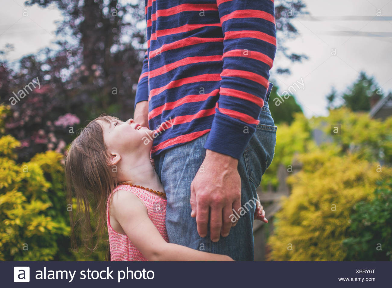 Daughter holding father's legs, looking up - Stock Image