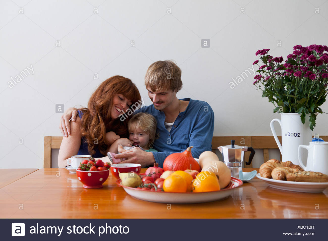A young family sitting side by side having breakfast - Stock Image