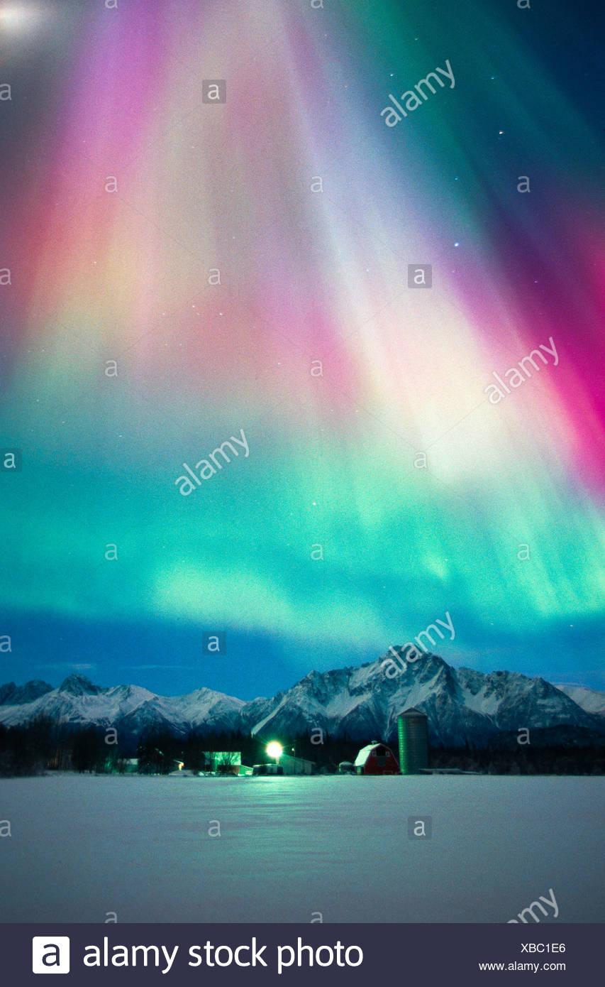 Alaska, Palmer. Aurora Borealis glow above a barn in the Matanuska Valley. - Stock Image