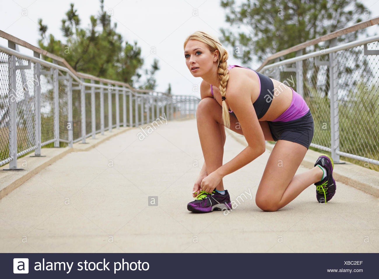 Woman tying shoe lace on bridge - Stock Image