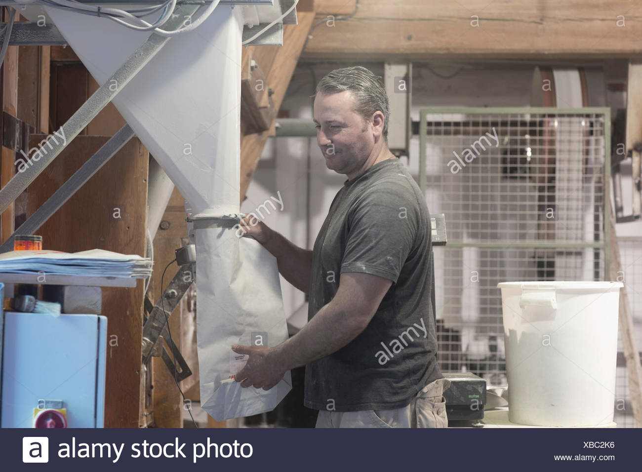 Male miller filling sacks with milled flour in wheat mill Stock Photo