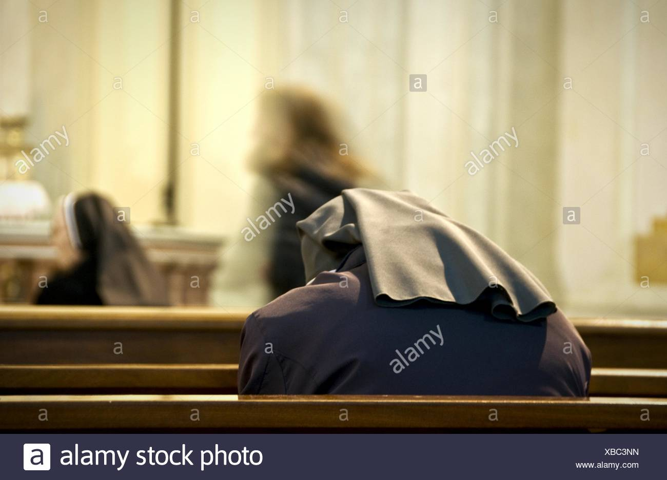 Rear View Of Nun Praying At Church - Stock Image