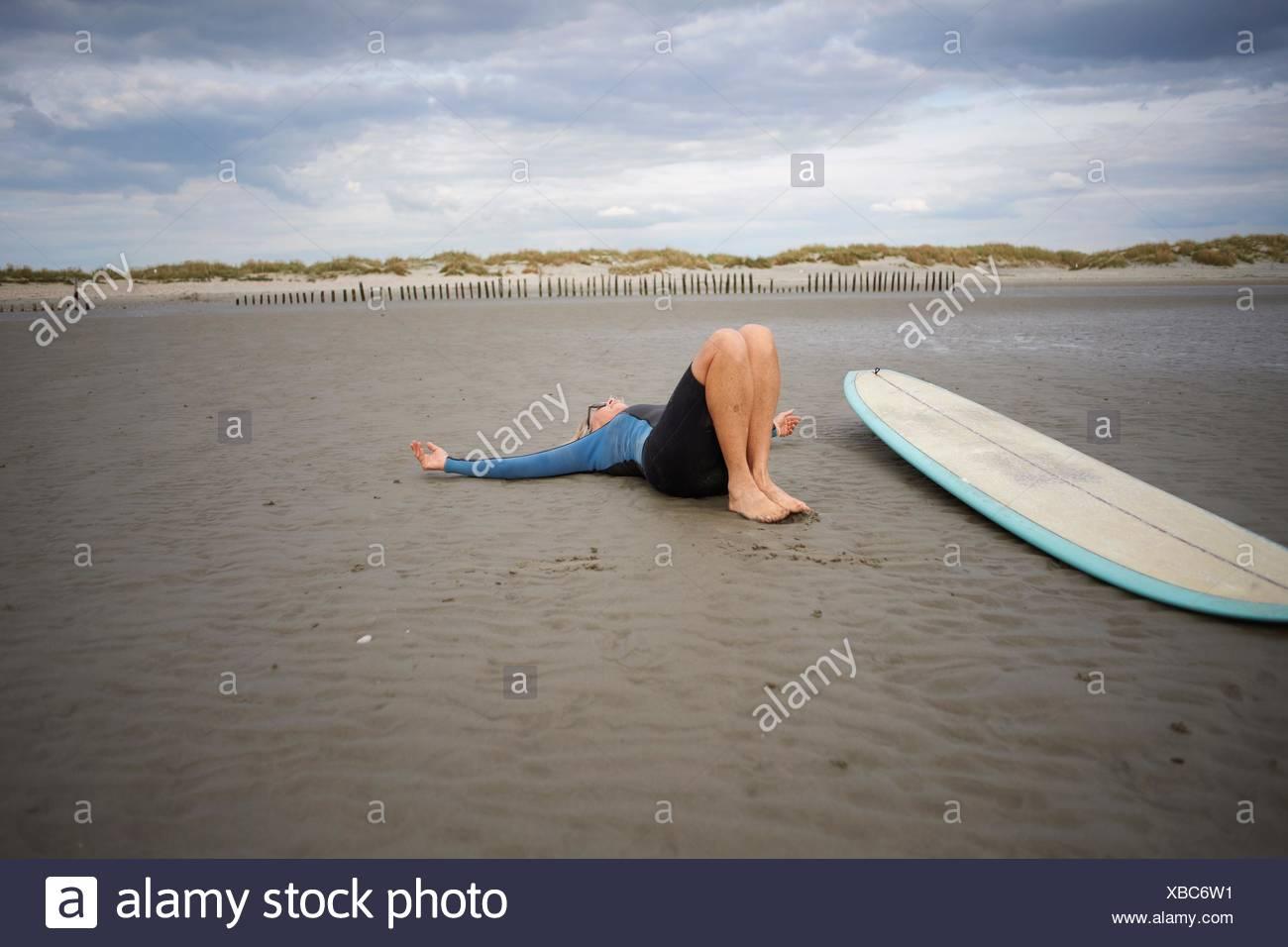Senior woman relaxing on sand, surfboard beside her - Stock Image