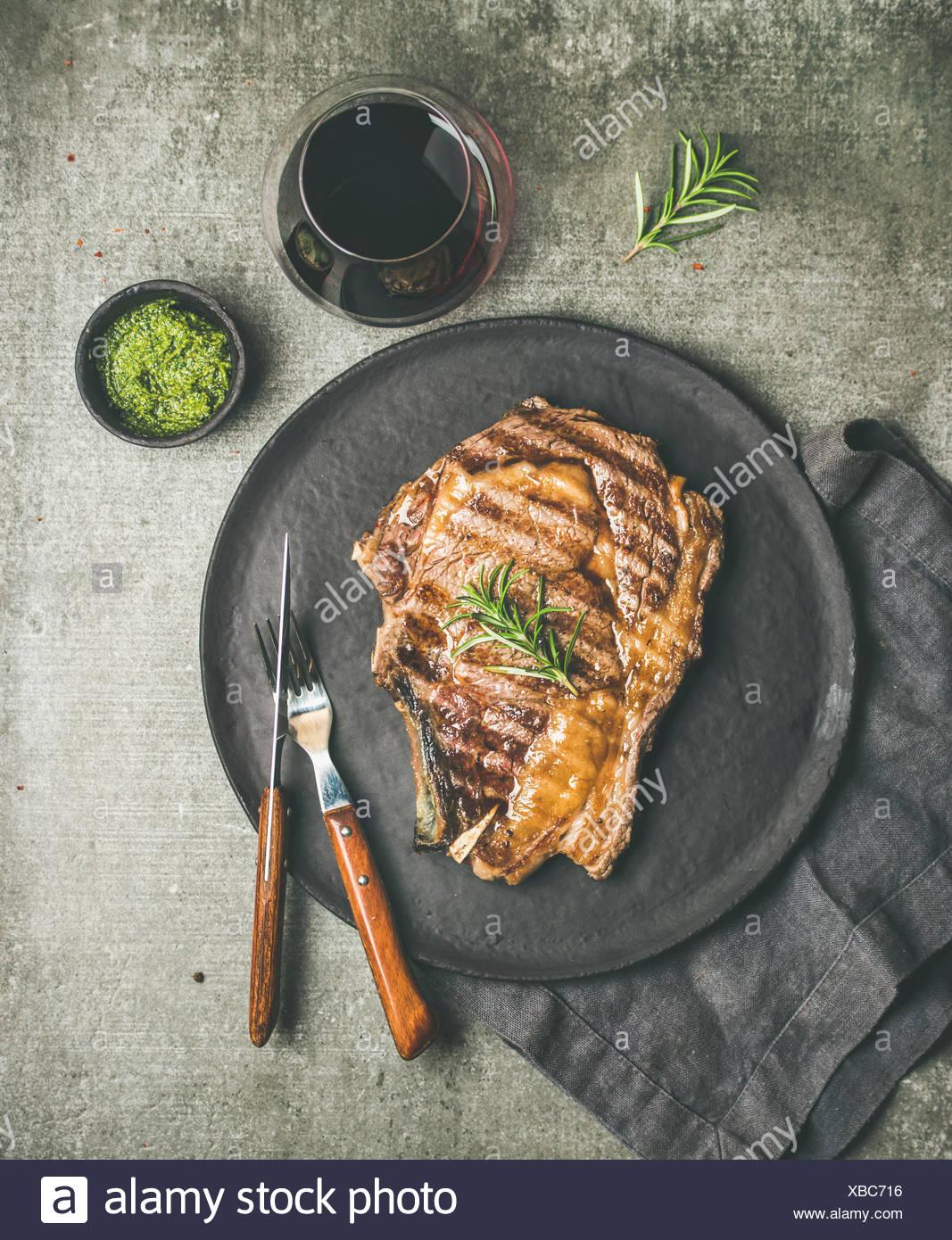 Flat-lay of Grilled hot rib-eye beef steak on bone with chimichurri