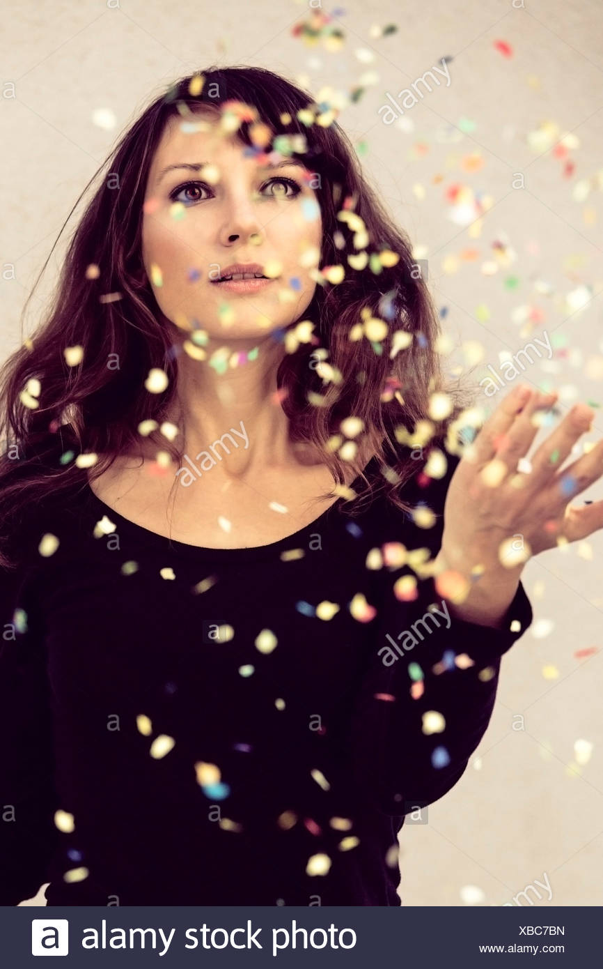 Young woman looking at confetti in the air - Stock Image