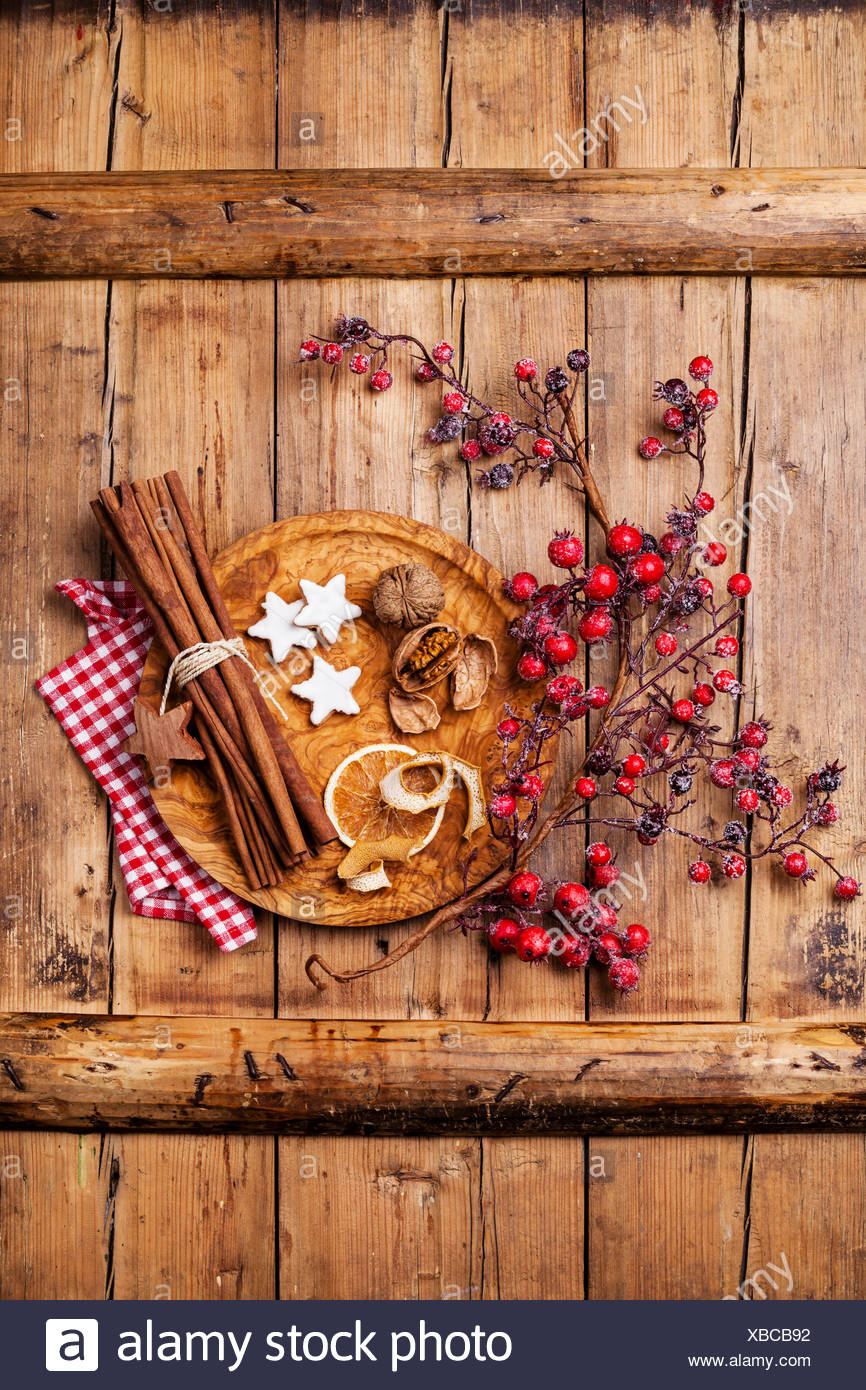 Xmas cookies, walnuts, dried orange peel, cinnamon sticks and branch with red berries on wooden texture background - Stock Image