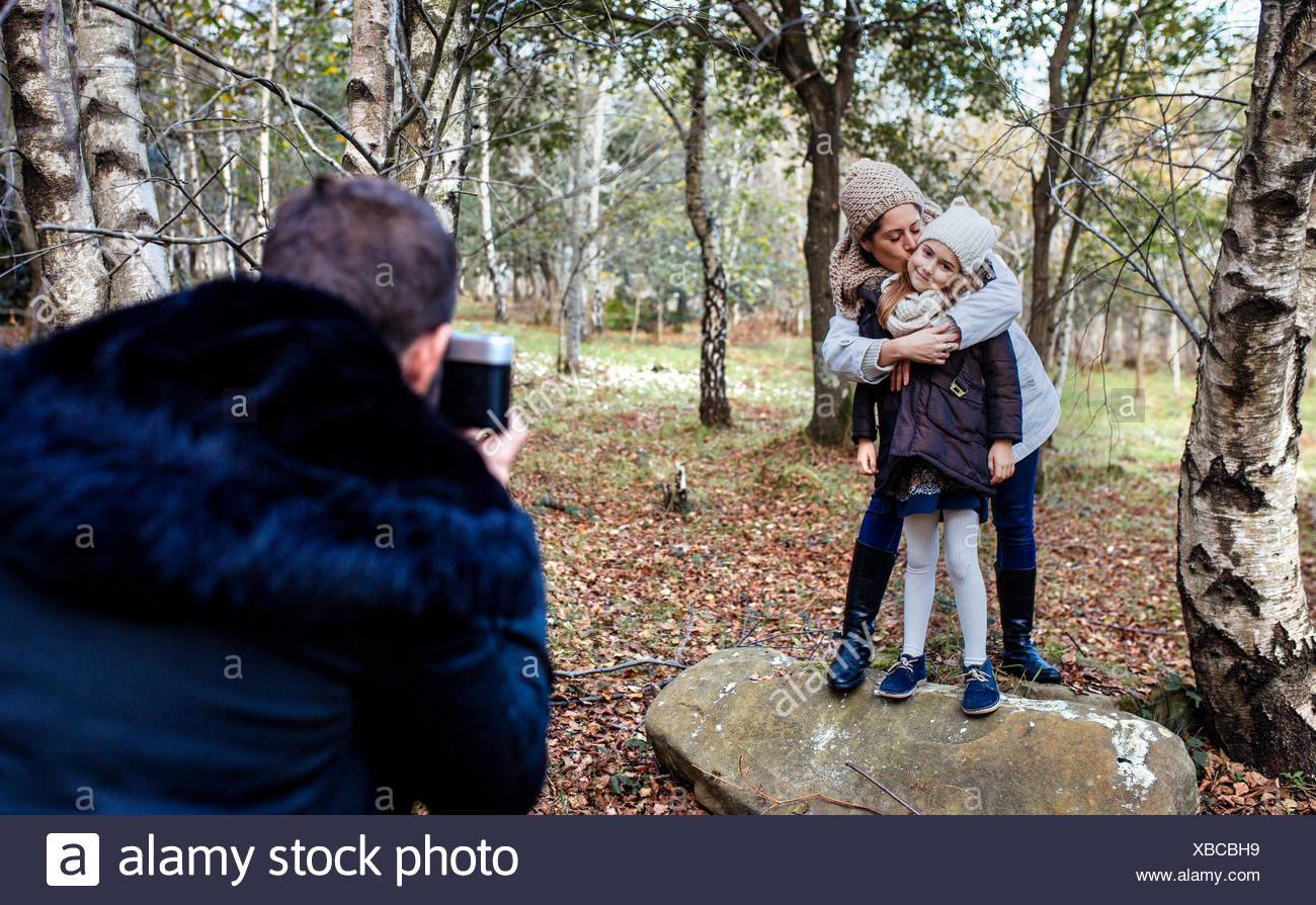 Father taking picture of wife and daughter in the forest - Stock Image