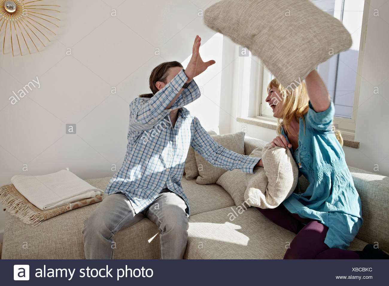 A Couple Pillow Fights In Their Living Room - Stock Image