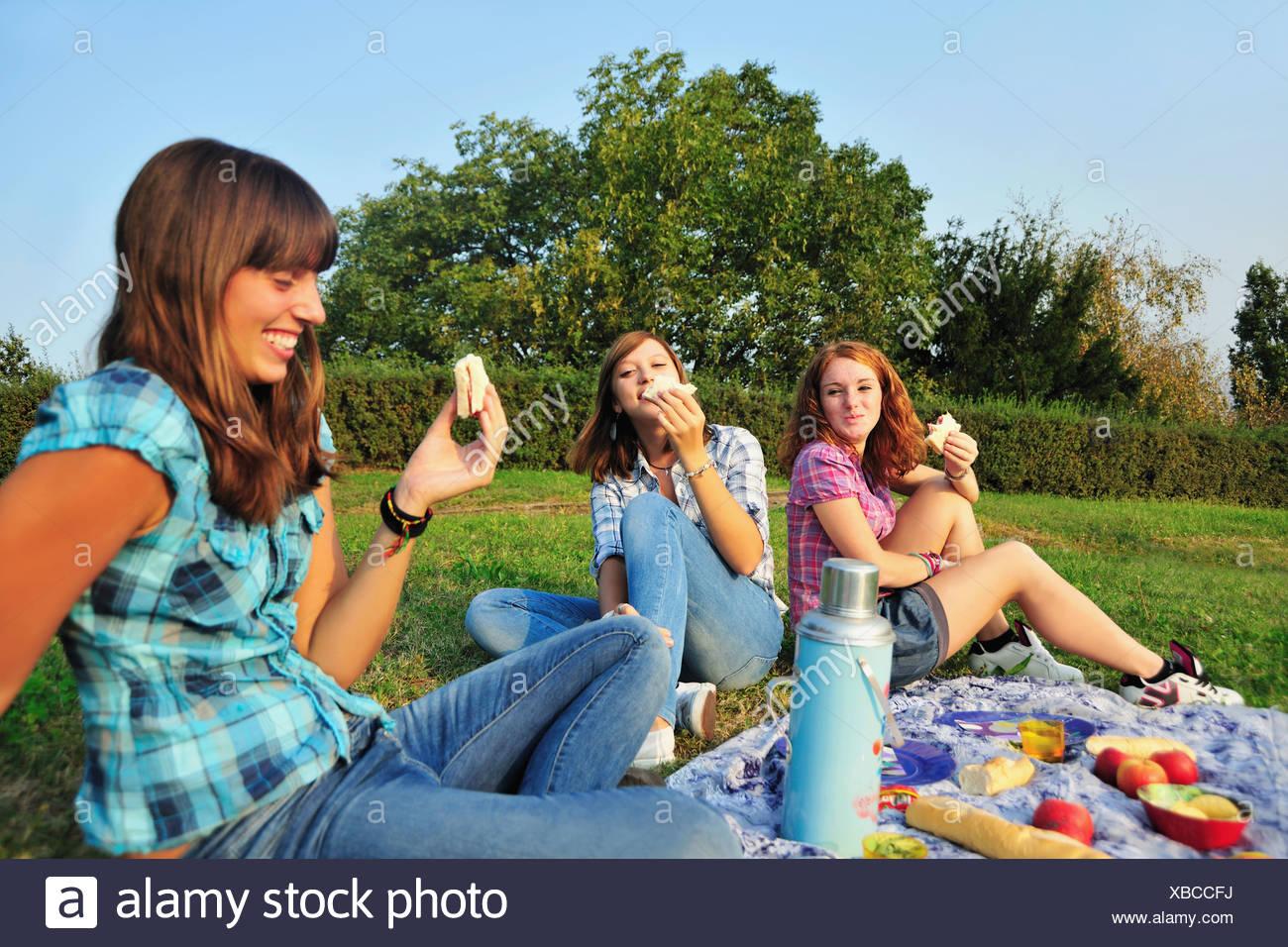 Teenage girls picnicking in rural field - Stock Image