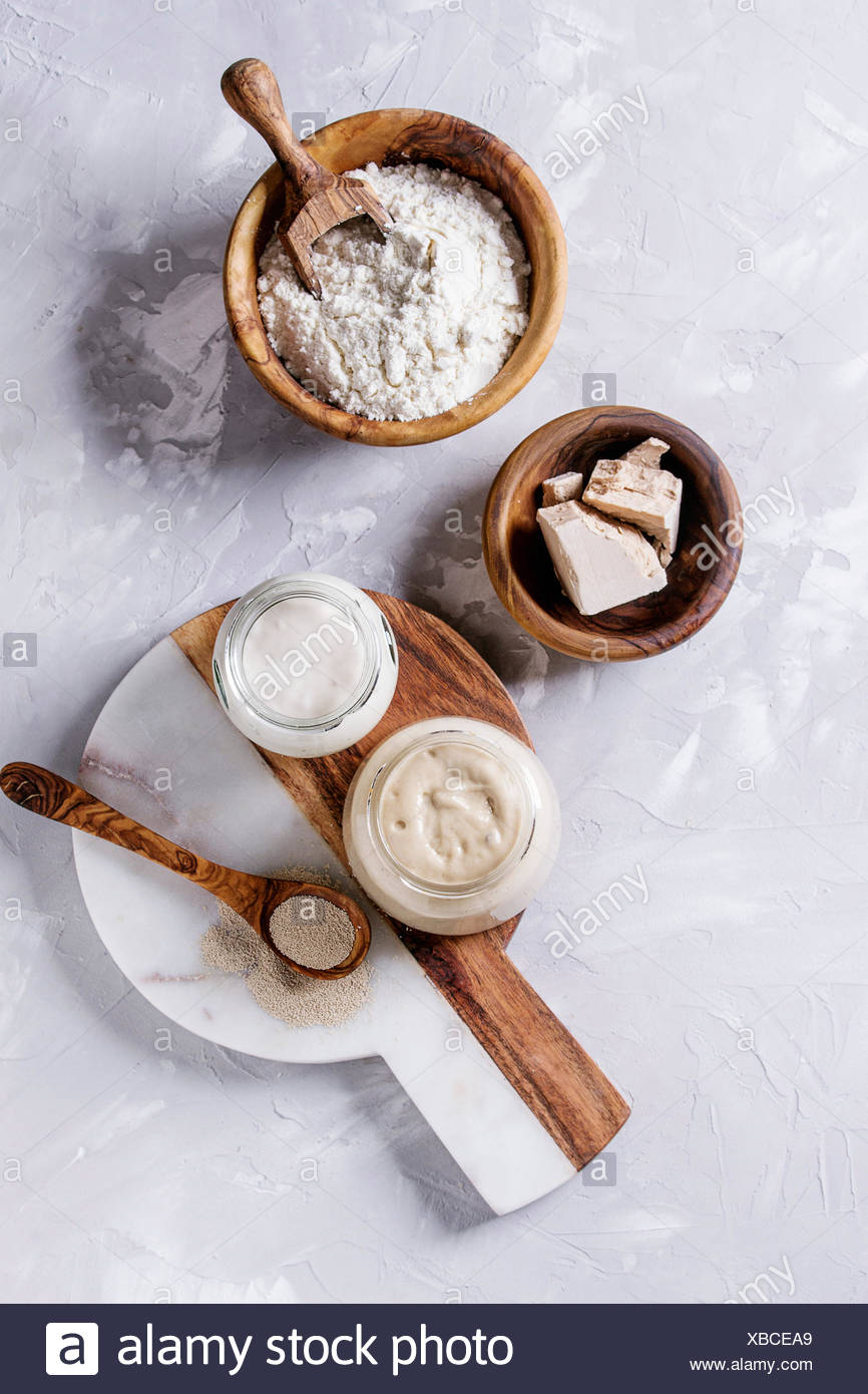 Rye and wheat sourdough in glass jars, fresh and instant yeast, olive wood bowl of flour for baking homemade bread. With spoon, serving board over gra - Stock Image
