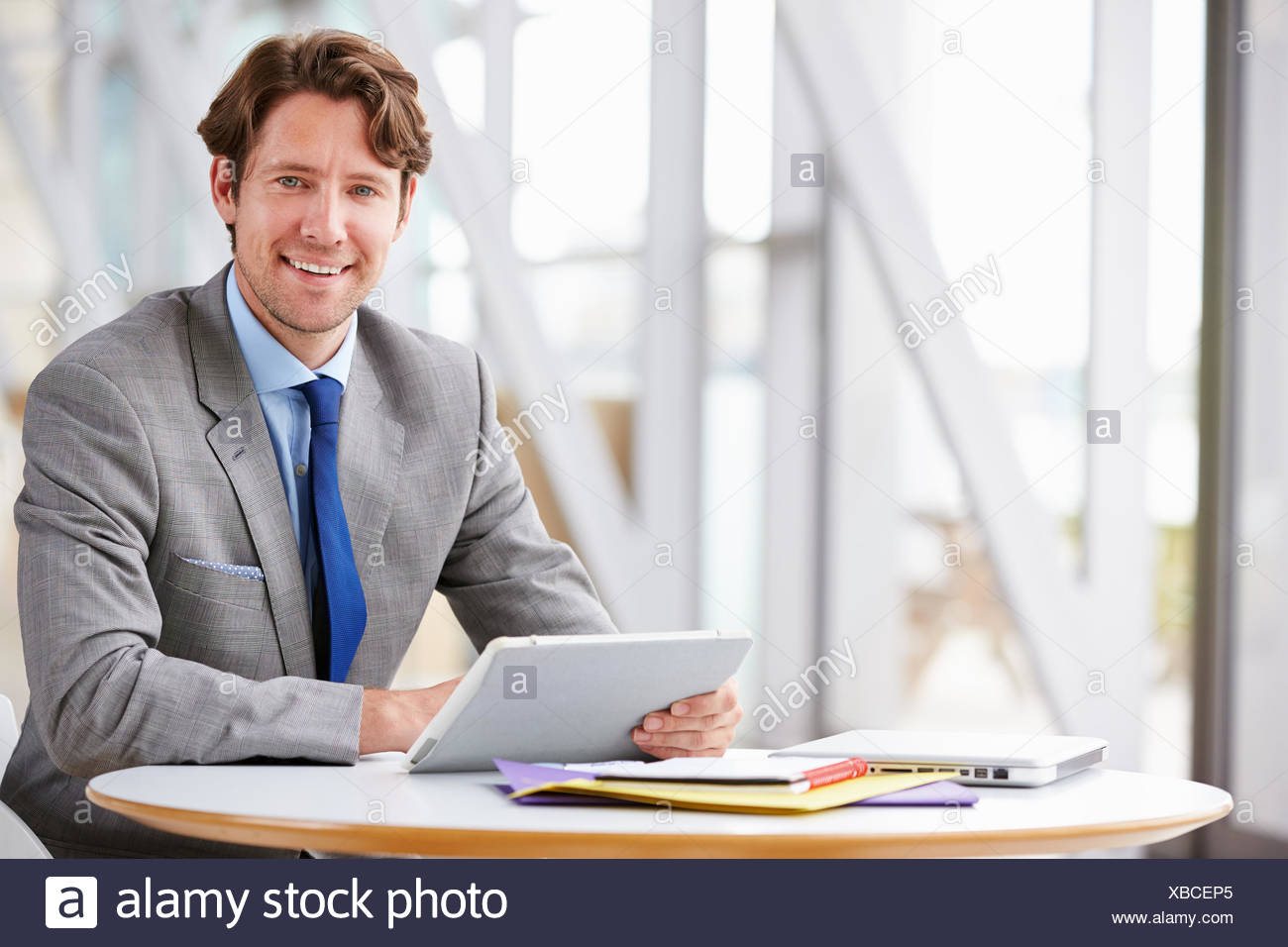 Corporate businessman working with tablet computer - Stock Image