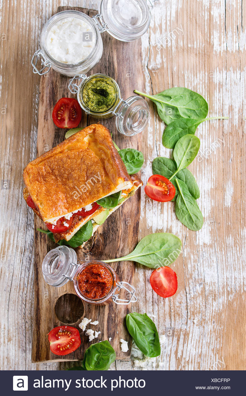 Low-carb gluten free Cloud bread veggie sandwich with spinach, avocado, feta cheese, tomatoes and pesto sauce, served on cutting - Stock Image