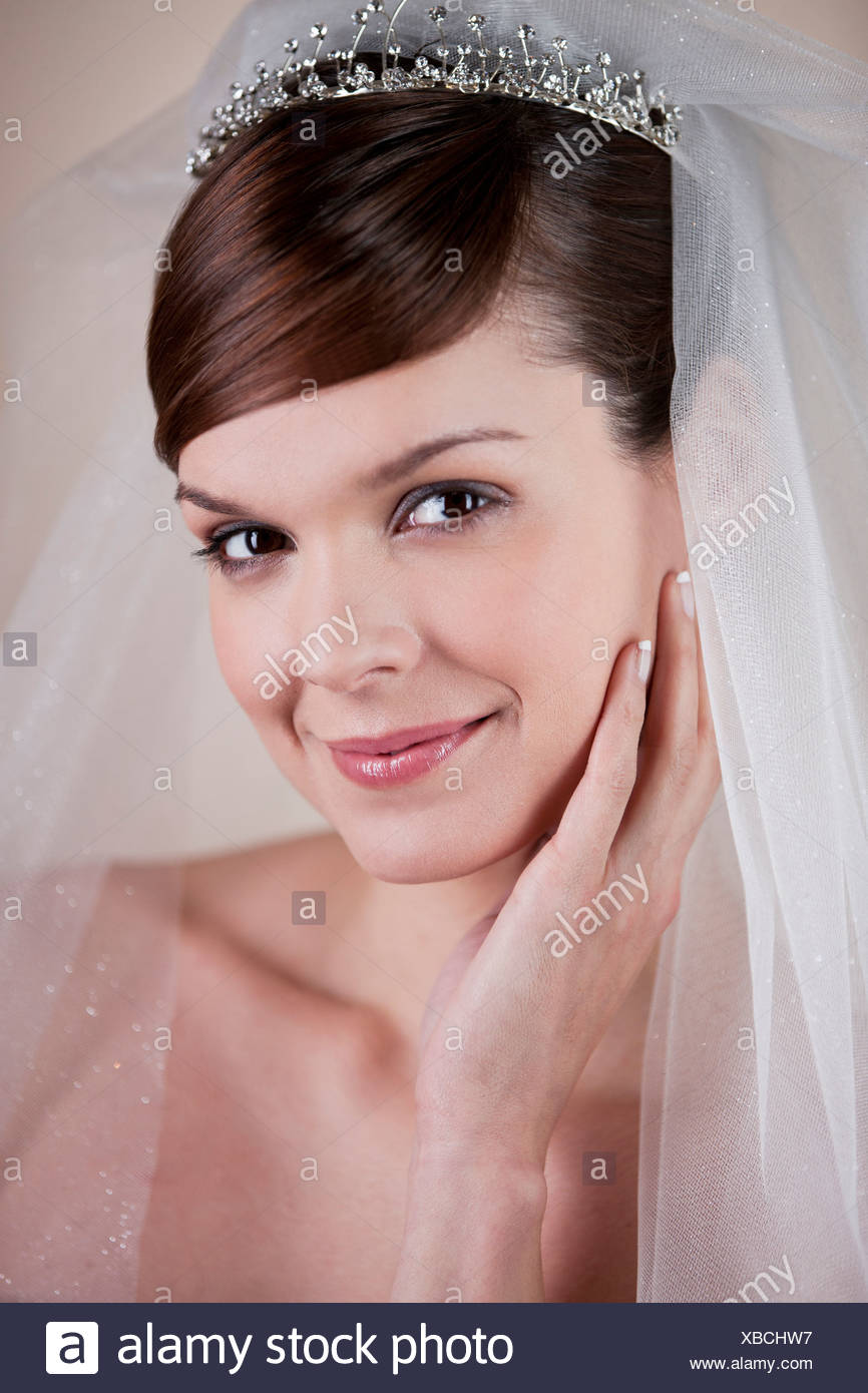 A young bride wearing a tiara and veil, hand on resting on her face Stock Photo