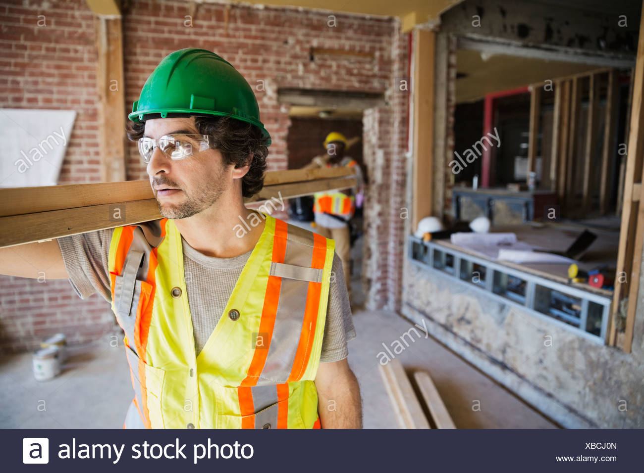 Tradesmen carrying lumber at construction site Stock Photo