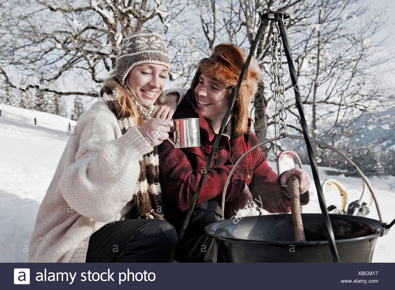 Austria, Salzburger Land, Couple cooking on campfire - Stock Image