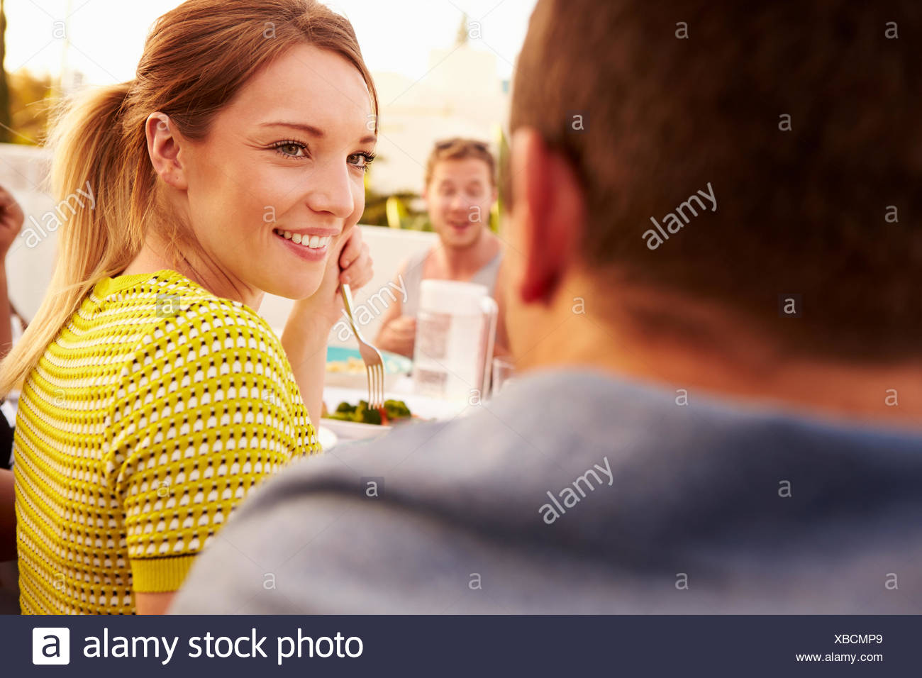 Couple Enjoying Outdoor Summer Meal With Friends - Stock Image